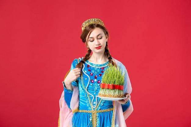 Portret pięknej azerskiej kobiety w tradycyjnym stroju trzymającej nasienie na czerwono