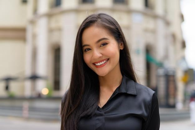 Portret pięknej azjatyckiej bizneswoman na zewnątrz na ulicy miasta uśmiecha się, patrząc pewnie