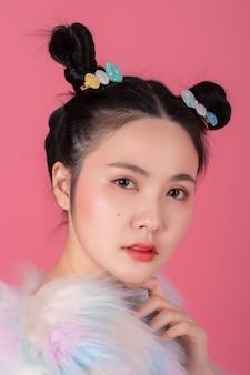 Portret pięknej azjatyckiej dziewczyny z makijażem artystycznym z fryzurą na różowo.