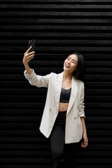 Portret pięknej azjatyckiej kobiety biorącej selfie na zewnątrz