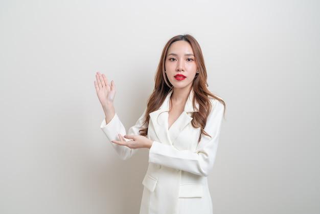 Portret pięknej azjatyckiej kobiety biznesu z ręką przedstawiającą lub wskazującą na białym tle