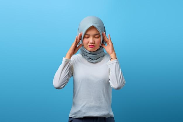 Portret pięknej azjatyckiej kobiety czuje się zdezorientowany i ból głowy na niebieskim tle