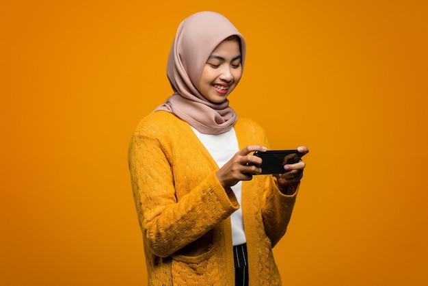 Portret pięknej azjatyckiej kobiety grającej w gry wideo na smartfonie z wyrazem szczęścia