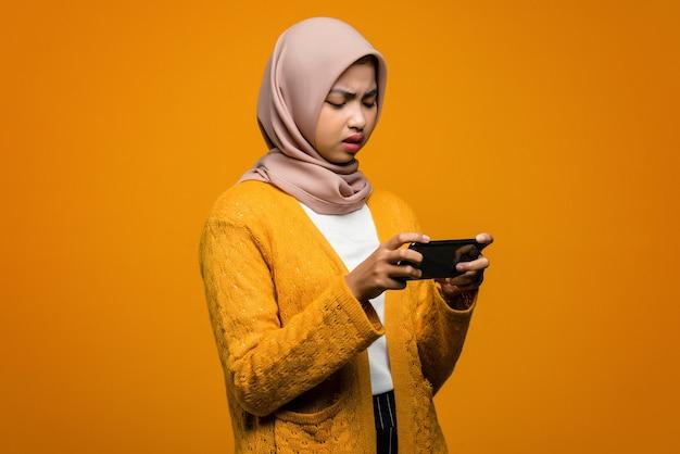 Portret pięknej azjatyckiej kobiety grającej w gry wideo na smartfonie z znudzonym wyrazem
