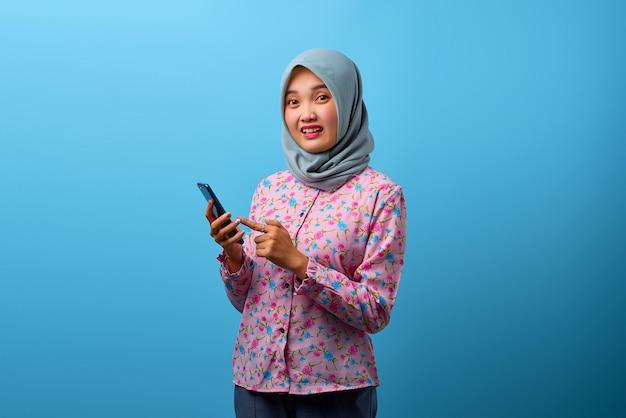 Portret pięknej azjatyckiej kobiety korzystającej z telefonu komórkowego ze zdezorientowanym wyrazem twarzy na niebieskim tle