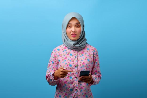 Portret pięknej azjatyckiej kobiety korzystającej z telefonu komórkowego ze zdezorientowanym wyrazem twarzy