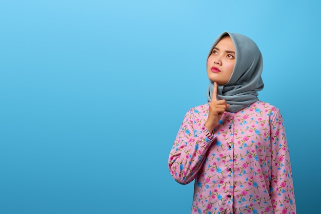 Portret pięknej azjatyckiej kobiety myślącej o zwątpieniu z palcem na brodzie i patrzącym w górę