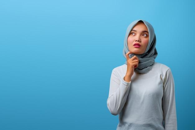 Portret pięknej azjatyckiej kobiety myślącej ręką na podbródku