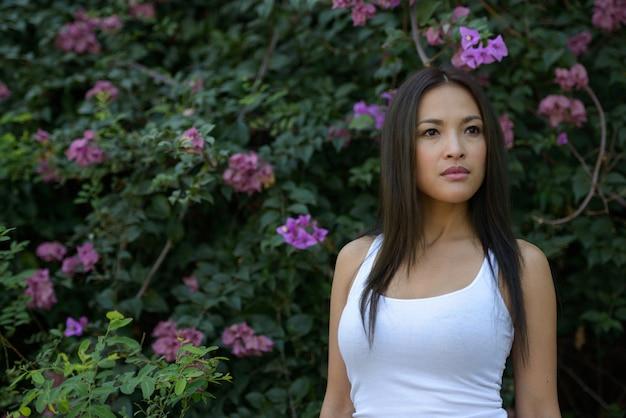 Portret pięknej azjatyckiej kobiety myśli w parku na świeżym powietrzu