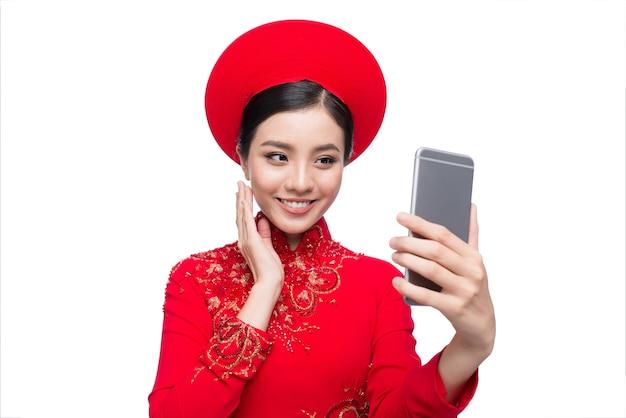 Portret pięknej azjatyckiej kobiety na tradycyjnym stroju festiwalowym ao dai robi zdjęcie selfie przez smartfona