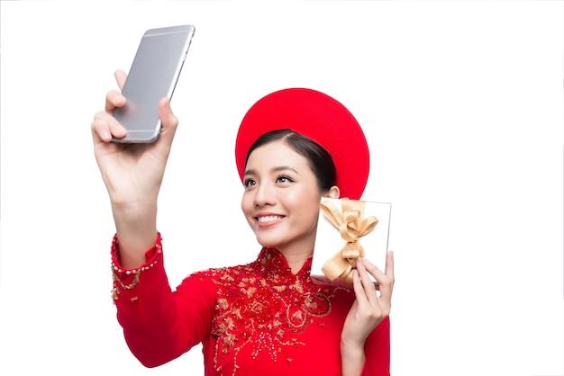 Portret pięknej azjatyckiej kobiety na tradycyjnym stroju festiwalowym ao dai trzymającego pudełko z prezentem robiącym zdjęcie selfie przez smartfona