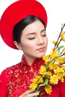 Portret pięknej azjatyckiej kobiety na tradycyjnym stroju festiwalu ao dai trzyma kwiat drzewa hoa mai (ochna integerrima). te wakacje. nowy rok księżycowy.