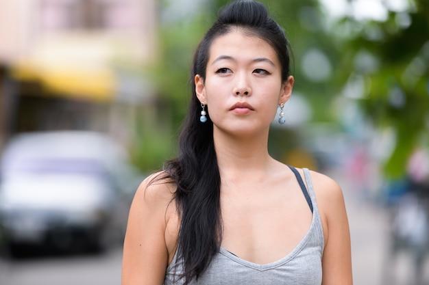 Portret pięknej azjatyckiej kobiety na ulicach na zewnątrz
