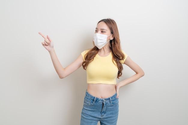 Portret pięknej azjatyckiej kobiety noszącej maskę z ręką przedstawiającą lub wskazującą na białym tle