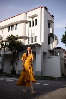Portret pięknej azjatyckiej kobiety pozującej w mieście podczas noszenia żółtej sukienki