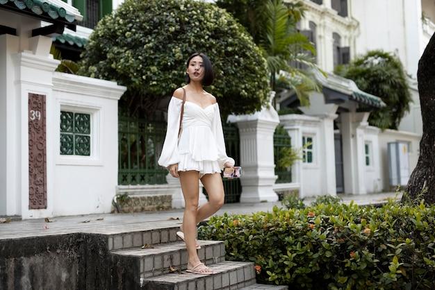 Portret pięknej azjatyckiej kobiety pozuje na zewnątrz w białej sukni