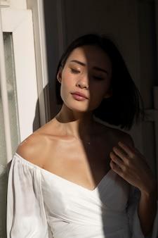Portret pięknej azjatyckiej kobiety pozuje na zewnątrz w cieniu