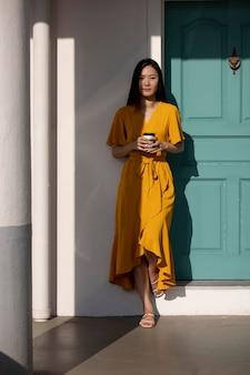 Portret pięknej azjatyckiej kobiety pozuje na zewnątrz w mieście przy kawie