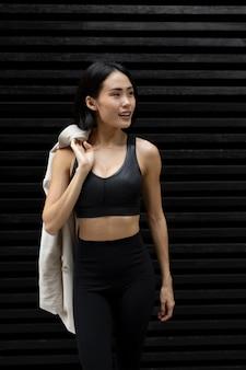 Portret pięknej azjatyckiej kobiety pozuje w athleisure na zewnątrz
