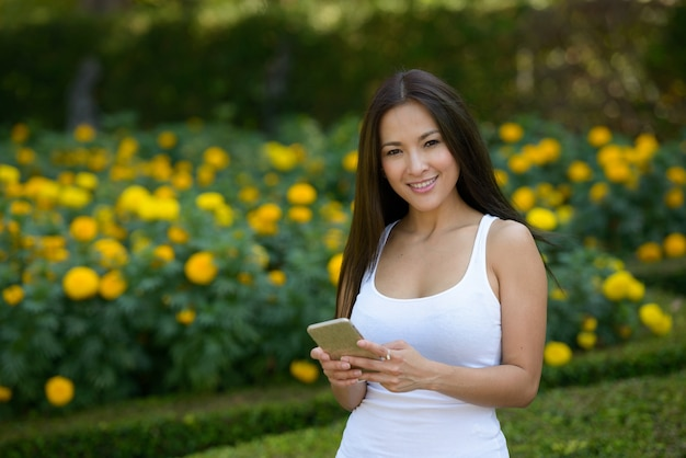 Portret pięknej azjatyckiej kobiety relaks w parku na świeżym powietrzu