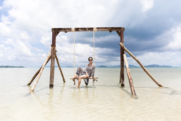 Portret pięknej azjatyckiej kobiety siedzącej na hamaku na morzu na wakacjach.