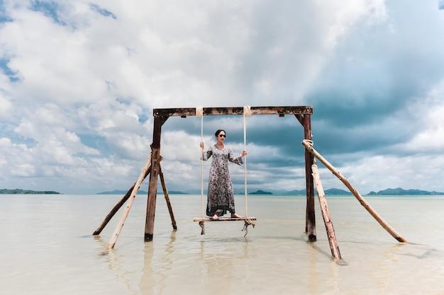 Portret pięknej azjatyckiej kobiety stojącej na hamaku na morzu na wakacjach.