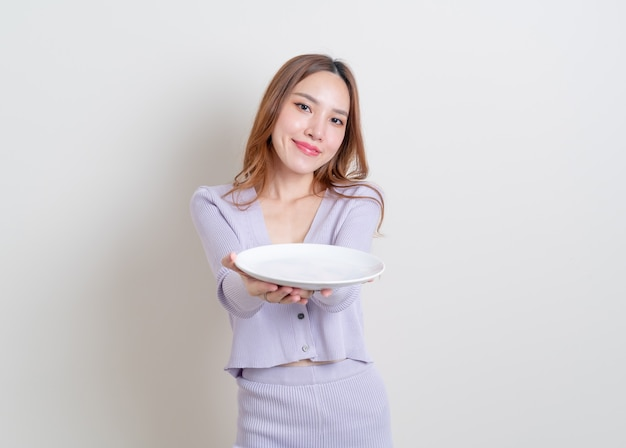 Portret pięknej azjatyckiej kobiety trzymającej pusty talerz na białym tle