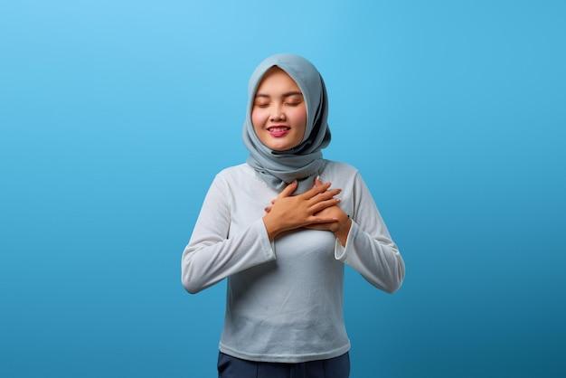 Portret pięknej azjatyckiej kobiety uśmiechającej się z rękami na klatce piersiowej z zamkniętymi oczami na niebieskim tle