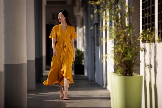 Portret pięknej azjatyckiej kobiety w żółtej sukience pozuje na zewnątrz w mieście