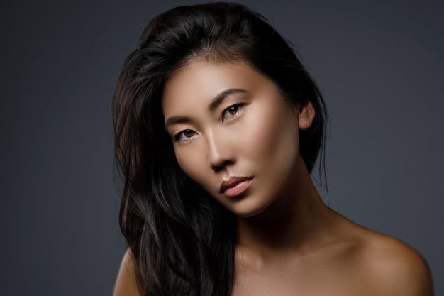 Portret pięknej azjatyckiej kobiety z czarnymi zdrowymi włosami