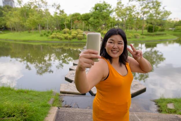 Portret pięknej azjatyckiej kobiety z nadwagą relaks w parku w mieście bangkok, tajlandia