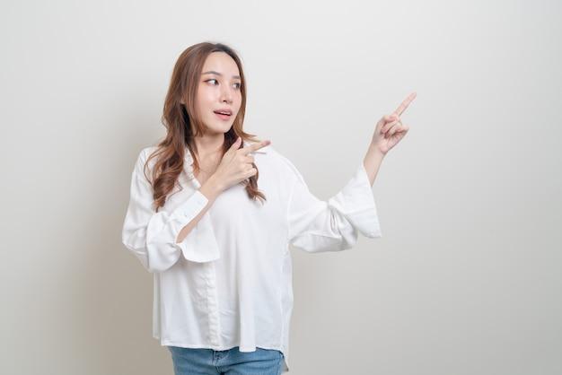 Portret pięknej azjatyckiej kobiety z ręką przedstawiającą lub wskazującą na białym tle