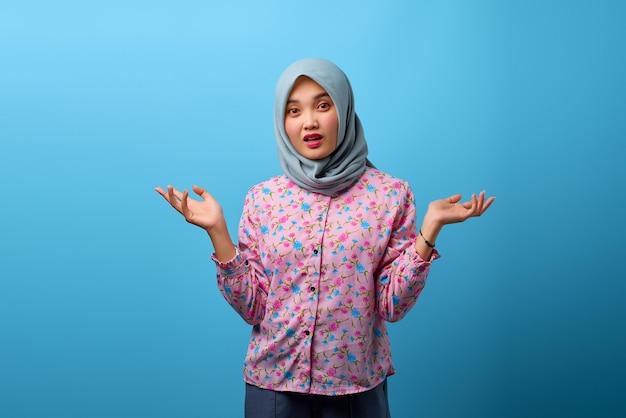 Portret pięknej azjatyckiej kobiety zaskoczonej zmieszanym i niezadowolonym wyrazem twarzy na niebieskim tle
