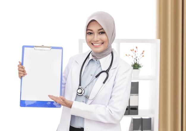 Portret pięknej azjatyckiej lekarki ze stetoskopem przedstawia czysty papier