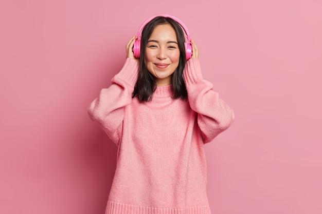 Portret pięknej azjatyckiej melomanki nosi bezprzewodowe, elektroniczne słuchawki stereo, słucha ulubionej ścieżki dźwiękowej lub popularnej piosenki odpoczywa przy dobrej muzyce, cieszy się spokojną melodią, nosi różowy sweter