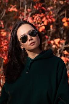 Portret pięknej azjatyckiej młodej kobiety w okularach przeciwsłonecznych w lesie jesienią o zachodzie słońca.