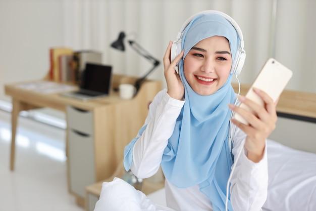 Portret pięknej azjatyckiej muzułmańskiej kobiety w bieliźnie oglądającej historię online na telefonie komórkowym, świeci na łóżku i łączy się z bezprzewodowym internetem. młoda śliczna kobieta z hijab słucha muzykę z telefonu