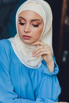 Portret pięknej azjatyckiej muzułmańskiej modelki na sobie białą bluzkę i niebieski hidżab, pozowanie na białej zasłonie jako tło w widoku z bliska