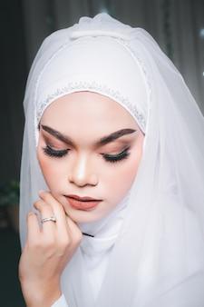 Portret pięknej azjatyckiej panny młodej muzułmańskiej z makijażem w białej sukni ślubnej i chustce hidżabu