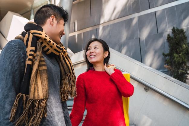 Portret pięknej azjatyckiej para korzystających z zakupów i wspólnej zabawy w centrum handlowym.