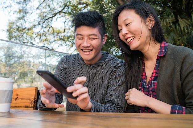 Portret pięknej azjatyckiej pary patrząc na telefon komórkowy siedząc i spędzając czas w kawiarni. koncepcja miłości i technologii.