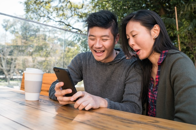 Portret pięknej azjatyckiej pary patrząc na telefon komórkowy siedząc i spędzając czas w kawiarni.