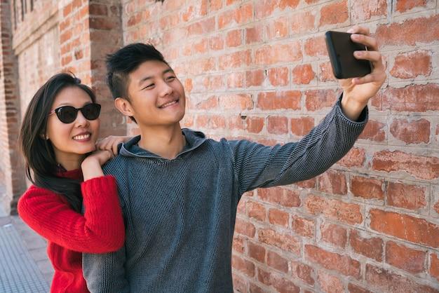 Portret pięknej azjatyckiej pary robienia selfie z telefonem komórkowym na zewnątrz na ulicy.