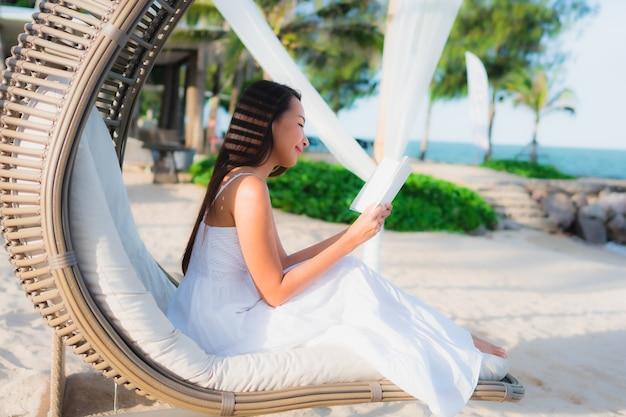 Portret pięknej azjatykciej kobiety czytelnicza książka wokoło plażowego dennego oceanu