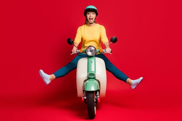 Portret pięknej beztroskiej dziewczyny jeżdżącej na motorowerze zabawy na czerwonej ścianie