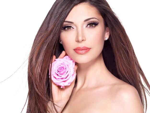 Portret pięknej białej ładnej kobiety z długimi prostymi włosami i różową różą na twarzy.