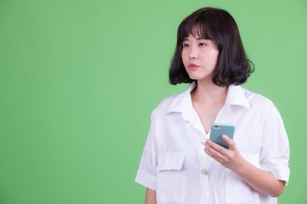 Portret pięknej bizneswoman azjatyckiego z krótkimi włosami przed chroma key lub zieloną ścianę