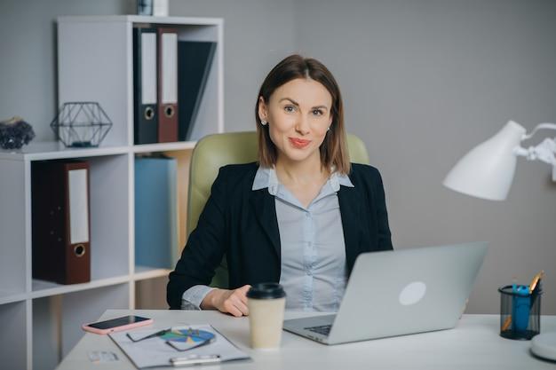 Portret pięknej bizneswoman siedząc przy biurku. udana i szczęśliwa kobieta świętuje rekordową sprzedaż