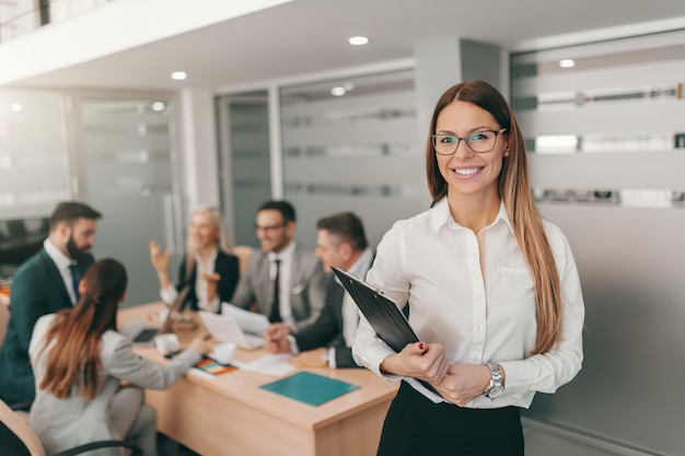 Portret pięknej bizneswoman w wizytowym, z długimi brązowymi włosami i okularami, trzymając schowek, stojąc w sali konferencyjnej.