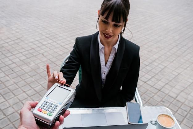 Portret pięknej bizneswoman za pomocą karty kredytowej do płatności w kawiarni na świeżym powietrzu